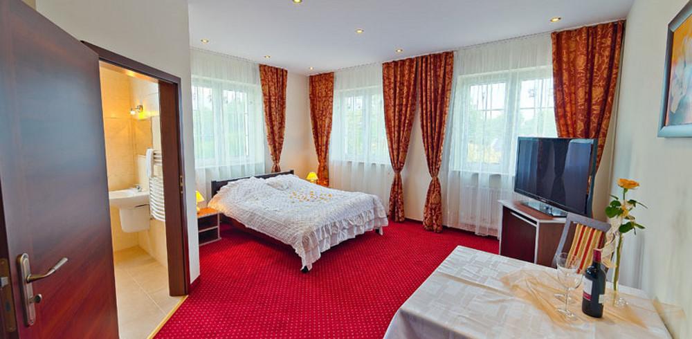 Widok na pokój hotelowy w Hotelu Kaprys. Pokój jest bardzo jasny i przytulny. Znajduje się w nim łoże małżeńskie.