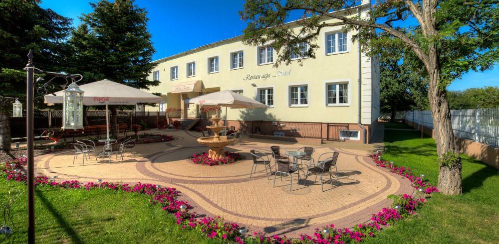 Widok na fontannę i stoliki ustawione w ogrodzie Hotelu Kaprys. Piękna słoneczna pogoda, błękitne niebo.